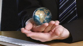 Businessman with a rotary terrestrial globe in his hand Stock Photos