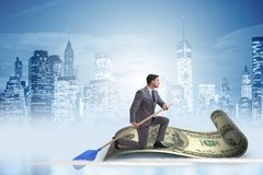 The businessman rowing on dollar boat in business financial concept. Businessman rowing on dollar boat in business financial concept Stock Photos
