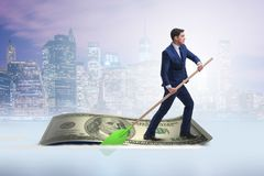 The businessman rowing on dollar boat in business financial concept. Businessman rowing on dollar boat in business financial concept Stock Image