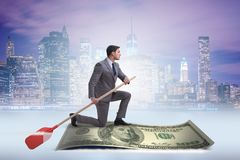 The businessman rowing on dollar boat in business financial concept. Businessman rowing on dollar boat in business financial concept stock photo