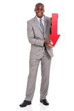 Businessman rrow pointing down. Portrait of afro american businessman holding red arrow pointing down on white background Royalty Free Stock Photo