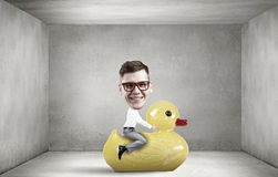 Businessman on rubber duck Royalty Free Stock Photography