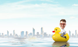 Businessman on rubber duck Stock Image