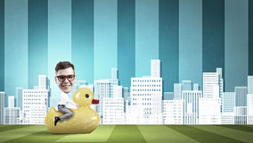 Businessman on rubber duck Stock Photo