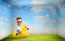 Businessman on rubber duck Stock Photography