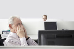 Businessman Rubbing Eyes In Office Cubicle Stock Photography