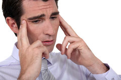 Businessman rubbing his temples Stock Photo
