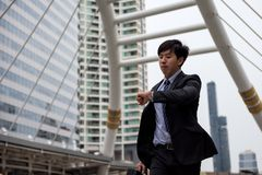 Businessman run and check time. Anxious Asian businessman run and look at watch to check time on city walk in rush hour. Young man late for train transportation Stock Images