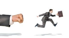Businessman runaway from big fist Royalty Free Stock Photos