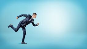 A businessman in a runner position ready to start on blue background. New business. Royalty Free Stock Photo