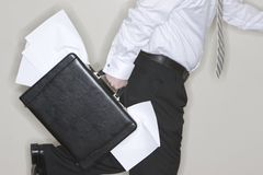 Businessman Running. Businessman with briefcase full of papers is running with the papers coming out of his briefcase Royalty Free Stock Images