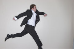 Businessman running. Through the office with his arms outstretched and jumping up and going Royalty Free Stock Image