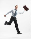 Businessman running. A studio view of a smiling businessman running and carrying an executive folder Stock Image