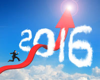 Businessman running arrow upward trend line through 2016 clouds. Businessman running on red arrow upward bending trend line breaking through 2016 shape clouds Stock Photo