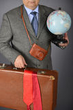 Businessman running as tourist. Man, dressed in formal suite runs with vintage suitcase and globus Stock Photos