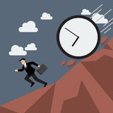 Businessman running away from clock attack Royalty Free Stock Photos
