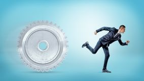 A businessman running away from a large metal spur gear on a blue background. Royalty Free Stock Photos
