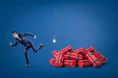 Businessman running away from pack of red tnt dynamite sticks with lighted fuse on blue background. Management and marketing. Financial risks. Business and vector illustration