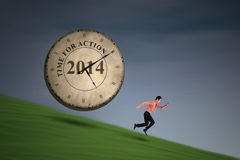 Businessman running with big time clock. Businessman is running with big time clock on top of a hill Stock Photography