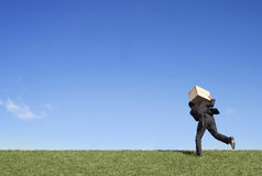 Businessman running with box Stock Photography