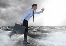 Businessman running with briefcase in sea of documents under sky clouds. Digital composite of Businessman running with briefcase in sea of documents under sky Royalty Free Stock Photography