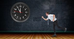 Businessman running with clock mounted on wall. Digital composite of Businessman running with clock mounted on wall Stock Photos