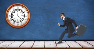 Businessman running with clock mounted on wall Stock Image