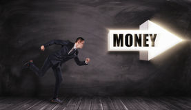 Businessman running in direction of big white arrow with title `MONEY`, pointing right Royalty Free Stock Photography