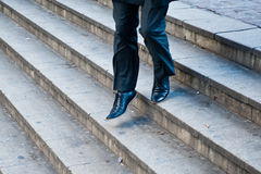 Businessman running down city stairs Royalty Free Stock Photo
