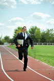 Businessman running fast on athletic track in work stress and urgency concept Stock Photo