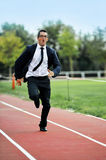 Businessman running fast on athletic track in work stress and urgency concept. Young businessman running fast on athletic track wearing suit and tie in work Royalty Free Stock Photography