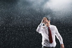 Businessman Running Fingers Through Wet Hair In Rain Stock Images