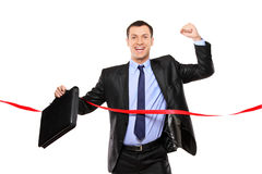 Businessman running at the finish line royalty free stock photo