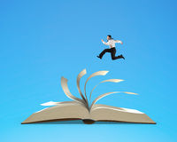 Businessman running on flipping pages of open book isolated in b. Businessman running on flipping pages top of open book isolated in blue background, 3D Royalty Free Stock Photos