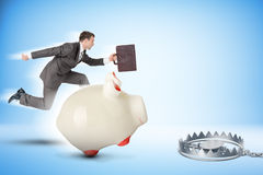 Businessman running forward with piggy bank. Businessman with piggy bank running forward to beartrap Royalty Free Stock Image