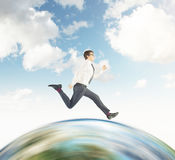 Businessman running on the globe with sky Stock Photo