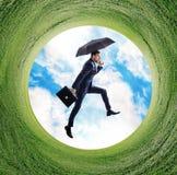 Businessman running into green grass circle. Royalty Free Stock Photo
