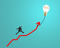 Businessman running on growth red arrow with glowing lamp balloo. N in green background Stock Image