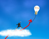 Businessman running on growth red arrow with glowing lamp balloon. Through cloud in the sky Royalty Free Stock Images