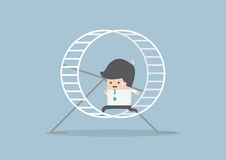 Businessman running in a hamster wheel Stock Image