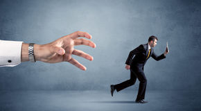 Businessman running from hand Royalty Free Stock Image