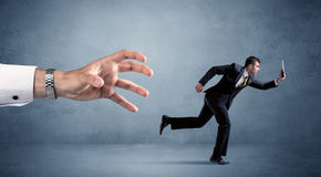 Businessman running from hand Royalty Free Stock Photography