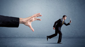 Businessman running from hand Royalty Free Stock Images