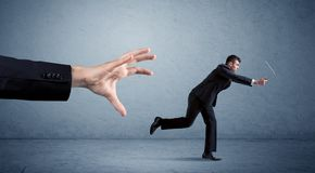 Businessman running from hand Stock Image