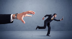 Businessman running from hand Stock Images