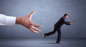 Businessman running from hand Stock Photo