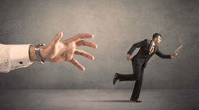 Businessman running from hand Stock Photography