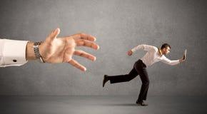 Businessman running from hand Stock Photos