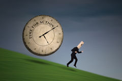 Businessman running on the hill. Anonymous businessman running chased by a big clock Stock Images