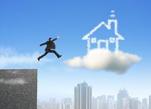 Businessman running and jumping on cloud dream house. With city background Stock Photo